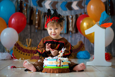 little cute boy in costume of American Indian Apache Chief sits and smash cake. Childrens holiday, happy Birthday 1 year, photo zone decoration.