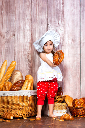 Eat fresh bread and homemade pastries. Little smiling girl in a cook cap with bagel in hand near a wicker basket with bread rolls and bakery products.