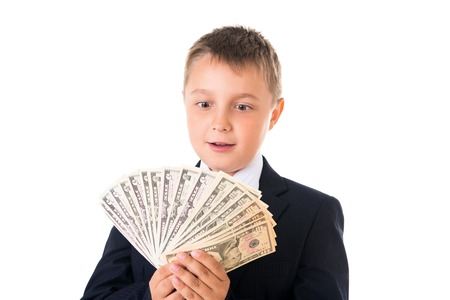 Young enterprising boy schoolboy in a business suit holding money in his hands. How to earn the first million dollars. Reklamní fotografie