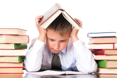 Un colegial cansado y rezagado se sienta en una biblioteca con libros y aprende lecciones. Falta de voluntad para aprender. Foto de archivo