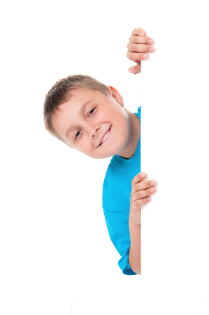 Smiling emotional positive teenager boy in bright blue t-shirt and posing behind a white panel isolated on white background. Place for advertising.