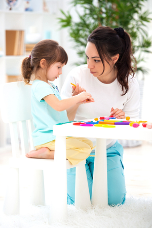 Mother helps a little daughter to sculpt figurines from plasticine. Childrens creativity. Happy family.