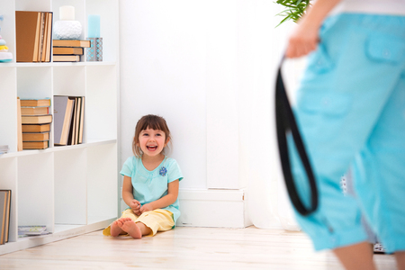 Parental punishment. Child abuse. Mom punish a little daughter with a belt and puts her in a corner. Stockfoto
