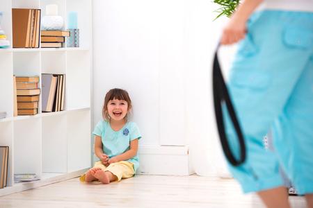 Punition parentale. Abus sur mineur. Maman punit une petite fille avec une ceinture et la met dans un coin.