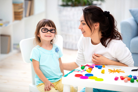 How to save healthy eyesight. Mom and daughter make glasses from plasticine. Stock Photo