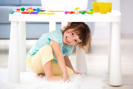 Little cute girl crawled under the table. The kid smiles, plays hide and seek. Reklamní fotografie - 122889284