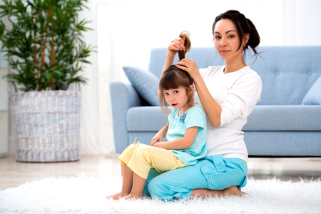 Happy loving family. Mother is combing her daughter's hair sitting on the carpet on the floor in the room. Imagens - 122009991