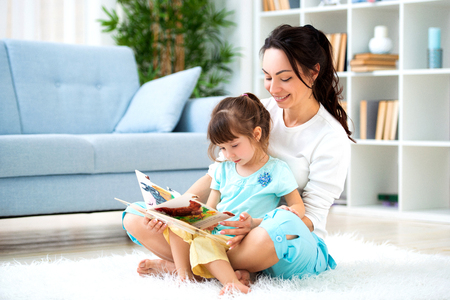 Pretty young mother reading a book to her daughter sitting on the carpet on the floor in the room. Reading with children Imagens - 122009966