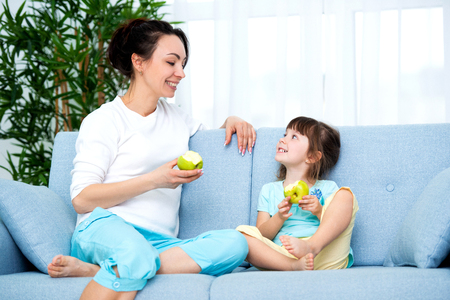 woman and little girl sitting on comfortable couch at home. Young mother talking communicates with small daughter. Best friends, happy motherhood