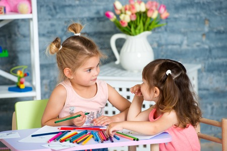 Two little beautiful girls draw with colorful pencils