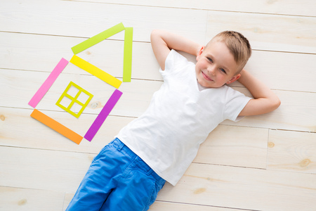 little boy lies on the floor next to a house of colored paper.