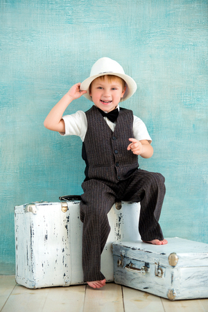 little boy gentleman in a hat is sitting on white retro suitcases. Serious boss businessman.