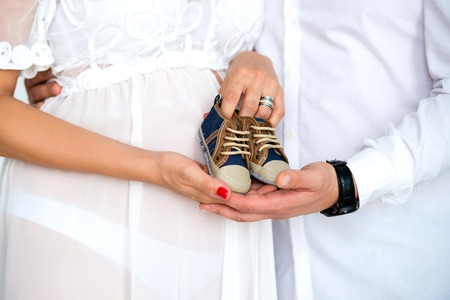 Close-up of a pregnant belly. Happy parents waiting for the son. Pregnant couple holding baby booties sneakers on tummy background.