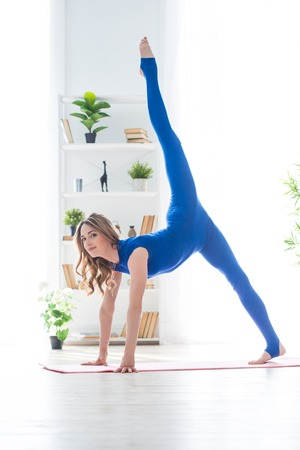 Young athletic girl fitness trainer in blue sports overalls shows morning gymnastic exercises in the interior. Twine in the air and swing a foot