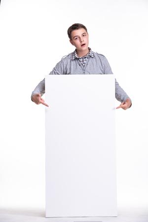 Cerca del hombre que muestra la pizarra. Chico adolescente, estudiante, colegial mostrando cartel de espacio vacío en blanco.