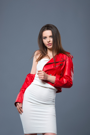 Fashionable style, fashion womens clothing, color combination. Beautiful brunette girl in white dress and red leather jacket isolated gray background.