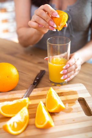 cooking, food and concept of veganism, vigor and healthy eating - close up of female hand squeeze fresh orange juice.