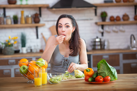 A hungry woman takes her hands and eats vegetables, stuffing them in her mouth. Healthy food.
