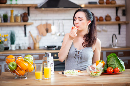 Beautiful young woman eats vegetable salad. The girl with pleasure puts a piece of fresh tomato in her mouth.
