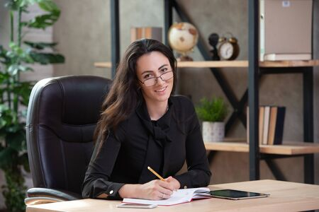 Beautiful stylish business woman with glasses sitting in an office at the table.