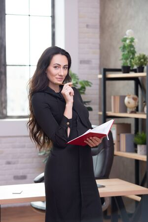 Beautiful stylish business woman in the office makes important entries in a red notepad. Female business planning and career growth.