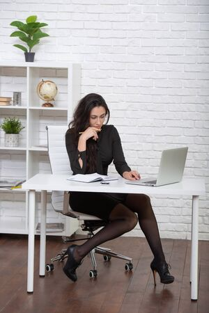 Beautiful stylish business lady working in a white office at a laptop. Womens business and modern technology.