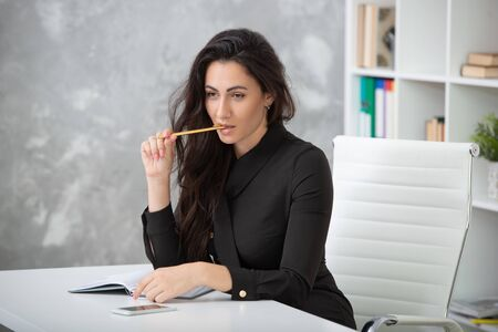 A brunette girl in a business black dress is sitting at a table in the office and is working hard. Student writes notes, takes notes in a notebook.