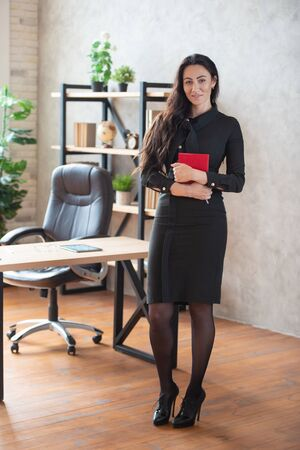 Beautiful stylish business woman with a red notebook in hand is standing in the office. Womens business and career. Stock fotó