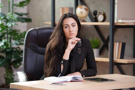 Beautiful stylish business woman with glasses sitting in an office at the table. Stock fotó