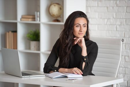 Beautiful stylish business lady working in a white office at the table. Female business planning and career growth. Stock fotó