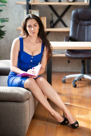 business lady in a blue dress is sitting on the sofa in the office and takes notes in a notebook. Work for women, lady boss, beauty consultant.