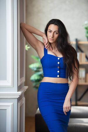 Beautiful business woman in a blue dress stands near the column in the office room.