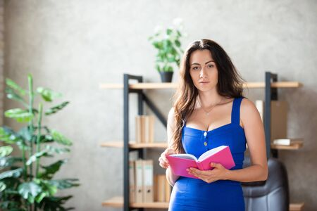 Beautiful business lady in a blue dress in the office with a notepad in her hands. Work for women. Stock fotó