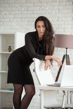 Business woman in a black dress is standing in an office, leaning on a chair.