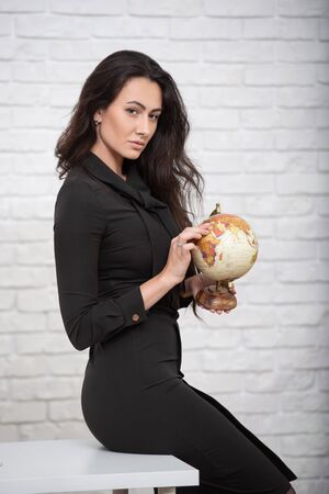 woman teacher in a strict business dress in an office setting with a globe in her hands. Stock fotó
