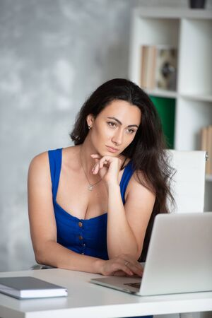 Beautiful businesswoman designer in blue dress looks into the laptop. Female business in the office