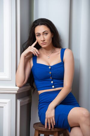 Office romance in the workplace. Seductive businesswoman secretary in blue dress sitting on a wooden stool
