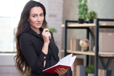 Beautiful stylish business woman in the office makes important entries in a red notepad. Female business planning and career growth Stock fotó
