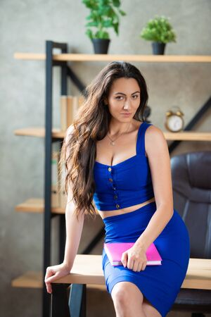 Beautiful business woman in a blue dress sitting on the desktop in the office with notepad in her hands. Work for women, lady boss, beauty consultant