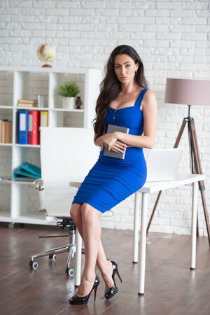 Beautiful businesswoman designer in blue dress greets clients in the office with a notebook in hand. Female business