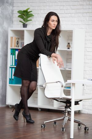 Business woman in a black dress is standing in an office, leaning on a chair