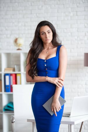 A beautiful businesswoman designer in a blue dress is standing in an office and is meeting customers. Female business Stock fotó