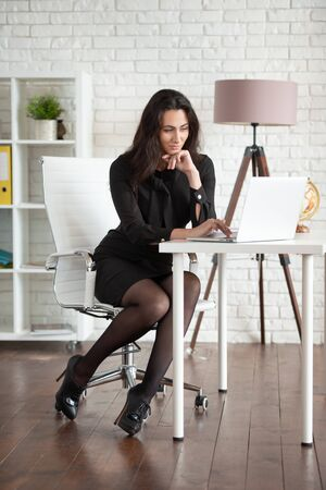 Business woman in a black dress works in the office on a laptop