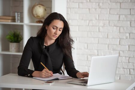 Beautiful stylish business lady working in a white office at a laptop. Womens business and modern technology Stock fotó