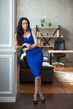 Beautiful business woman in a blue dress stands near the column in the office room