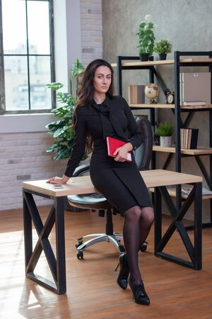Beautiful stylish business woman with a red notebook in hand is standing in the office. Womens business and career
