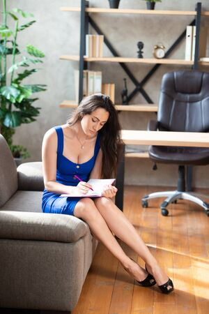 business lady in a blue dress is sitting on the sofa in the office and takes notes in a notebook. Work for women, lady boss, beauty consultant