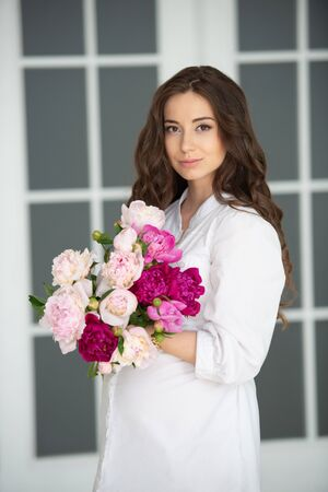 Close-up portrait of a beautiful young woman girl with gorgeous hair and a bouquet of peony flowers