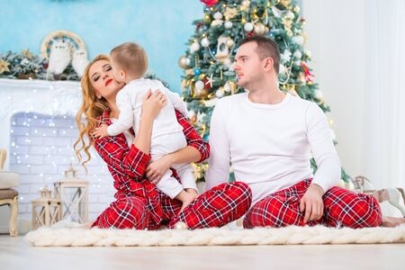 Happy smiling family in checkered pajamas near the Christmas tree and New Year's fireplace.