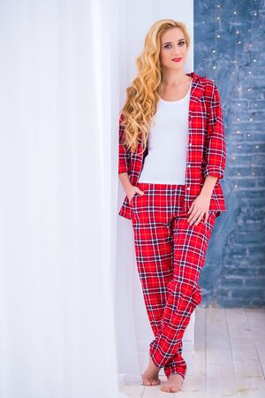 Beautiful blonde woman in red checkered pajamas stands near the window and demonstrates comfortable home clothes
